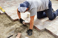 Laying down paver worker installer bricks on large patio Stock Photography