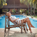 Laziness lazy day idleness woman sleeping in the deck chair near the swimming pool Stock Photos