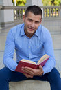 Laziness picture of a handsome man reading an interesting book Royalty Free Stock Photos