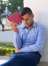 Laziness picture of a handsome man reading an interesting book Royalty Free Stock Image