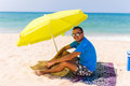 Lazing man in sun  under solar umbrella on towel enjoy the lazy time on the beach Royalty Free Stock Photo