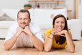 Lazy attractive young couple unwinding at home lying on their stomachs on the wooden floor in the living room grinning the Stock Image