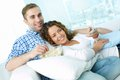 Lazy lovers young enjoying weekend watching tv and eating pop corn Stock Photos