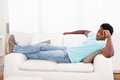 Lazy man chilling out on sofa worried african young sitting couch at home Royalty Free Stock Photo
