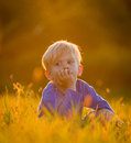 Lazy summer day a toddler sits lazily in a field of grass with an expression on deep thought Stock Photo