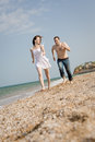 Le couple attrayant fonctionne le long de la plage Image stock