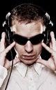 Le DJ beau dans des lunettes de soleil avec des écouteurs Image stock