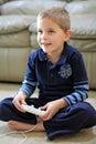 Le garçon joue le jeu vidéo tenu dans la main Image stock