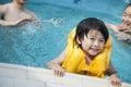 Le portrait du fils de sourire dans l eau et se tenir sur les piscines affilent avec la famille à l arrière plan Photo libre de droits