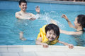Le portrait du fils de sourire dans l eau et se tenir sur les piscines affilent avec la famille à l arrière plan Photos stock