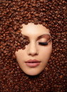 Le visage de la fille s'est noyé en grains de café Photo stock