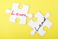 Lead or learn and words written on two pieces of jigsaw puzzle Royalty Free Stock Image
