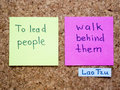 Lead people famous lao tzu quote interpretation with sticker notes on cork board Stock Photography