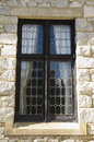 Leaded glass window in stone wall an antique sits a Royalty Free Stock Photography
