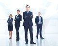 Leader and team portrait of young businessman looking at camera with elegant partners on background Royalty Free Stock Photography