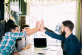 stock image of  We are leaders on the market. Cheerful young people giving each other high-five with smile while sitting at the office table on bu