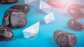 Leadership white paper boat lead further ships between abstract rock stones on blue background. Light flares right top Royalty Free Stock Photo