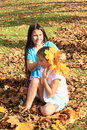 Leaf fashion girls barfoot kids one smiling girl is combing hair of another one and decorating her with maple leaves Stock Photography