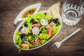 Leafy green mixed salad on a grunge wood table healthy with fresh spring ingredients with savory oil dressing view from Royalty Free Stock Photography
