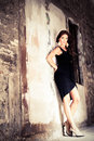 The lean a beautiful brunette woman leaning against an old wall with her hands behind her back wearing a little black dress and Stock Image