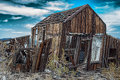Leaning rundown cabin with dramatic sky in background in randsberg california Stock Image