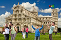 Leaning Tower of Pisa tourists habits behavior. Italian monuments. Flag. Royalty Free Stock Photo