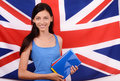 Learn english beautiful student holding books blue blank book cover young woman standing with the uk flag in the background Royalty Free Stock Images