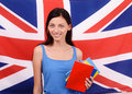 Learn english beautiful student holding books red blank book cover young woman standing with the uk flag in the background Stock Photo