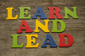 Learn and lead text on a wooden background Stock Photo