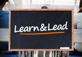 Learn and lead written on blackboard in a classroom Royalty Free Stock Photo