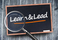 Learn and lead written on a blackboard with magnifying glass Stock Photos