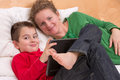 Learning with comfort from his mother in the bed on the laptop Royalty Free Stock Photos