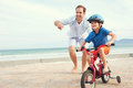Learning to ride a bike father and son bicycle at the beach having fun together Royalty Free Stock Photo