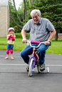 Learning to ride a bike with training wheels an older man takes his granddaughters for complete still fun Royalty Free Stock Photography