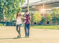 Learning to skateboarding young playful couple having a romantic date outdoors sportive men teaching her girlfriend teen lovers Royalty Free Stock Images