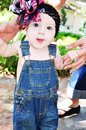 Learning to walk toddler baby in blue overalls is by holding mothers fingers Royalty Free Stock Photography