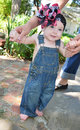 Learning to walk toddler baby in blue overalls is by holding mothers fingers Royalty Free Stock Photos