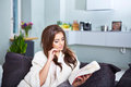 Leasure and home concept calm teenage girl woman reading book sitting on couch at Stock Photography