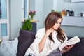 Leasure and home concept calm teenage girl woman reading book sitting on couch at Royalty Free Stock Image