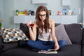 Leasure and home concept calm teenage girl woman reading book sitting on couch at Royalty Free Stock Photography