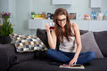 Leasure and home concept calm teenage girl woman reading book sitting on couch at Royalty Free Stock Images