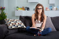 Leasure and home concept calm teenage girl woman reading book sitting on couch at Stock Photo