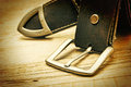 Leather belt with a buckle on wooden board Stock Photos