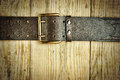 Leather belt with a buckle on wooden board toned Royalty Free Stock Images