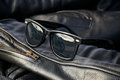 Leather jacket detail with sunglasses close up generic wayfarer on sleeve of buffalo hide motorcycle showing motorcycle in Stock Photo