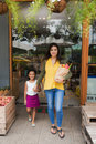Leaving grocery store pretty indian women with paper bag and her daughter Royalty Free Stock Photography