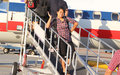 Leaving on a jetplane teenage filipino or asian female posed by commercial commuter plane waving goodbye Royalty Free Stock Images