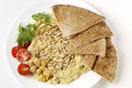 Lebanese hummus and pine nuts from above with on a plate with some flat bread sliced cherry tomatoes a garnish of young salad Royalty Free Stock Images
