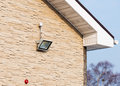 Led floodlight on wall of house covered with lite brown decorative slate stone surface Royalty Free Stock Photography