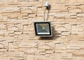 Led floodlight on wall of house covered with lite brown decorative slate stone surface Royalty Free Stock Images
